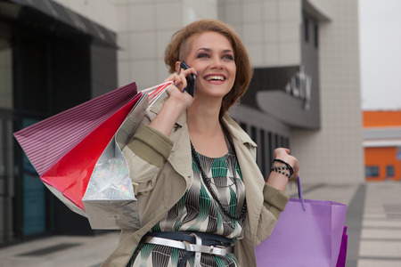 Shopping young beautiful happy girl with colored bags with phone in hand photo