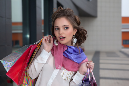 Shopping young beautiful happy girl with colored bags photo