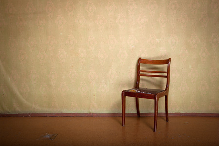 utilitarian: Antique ragged chair in old room interior with vintage wallpaper