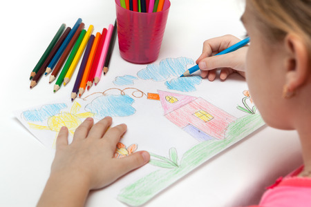 Child draws a pencil drawing of the world