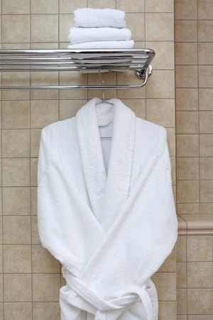 bath gown: White coat hanging on a metal rack with towels in the bathroom on the background tiles.