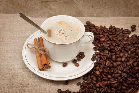 cinnamon sticks: A cup of hot coffee on coffee beans linen and cinnamon sticks