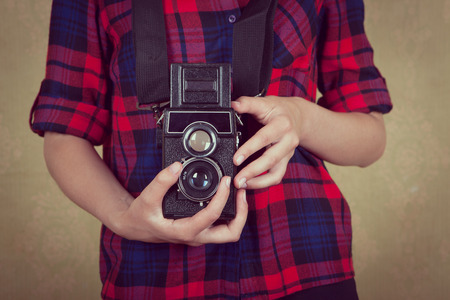 nonworking: Old vintage film camera in the hands of a young girl in a red plaid shirt standing near the old yellow wall. Stock Photo