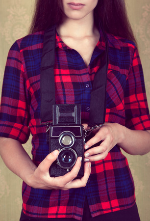 Old vintage film camera in the hands of a young girl in a red plaid shirt standing near the old yellow wall. Stock Photo