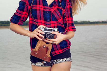Young girl photographer with old film camera in hands sitting on the river bank.