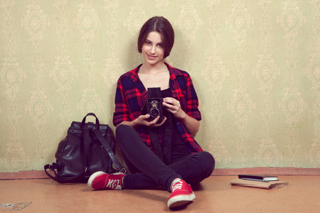 nonworking: Old vintage film camera in the hands of a young girl in a red plaid shirt sitting near the old yellow wall.