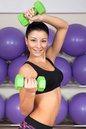 sorority: Fitness. Young girl athlete in the gym performing an exercise with a sports instrument occupies in his hands. Stock Photo