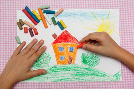 Child draws a pencil drawing of the peace. Green field, the bushes and the house. Archivio Fotografico