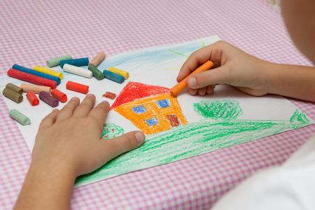 dessin enfants: Enfant dessine un dessin au crayon de la paix. champ vert, les buissons et la maison.