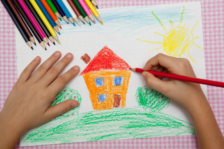 Child draws a pencil drawing of the peace. Green field, the bushes and the house. Фото со стока