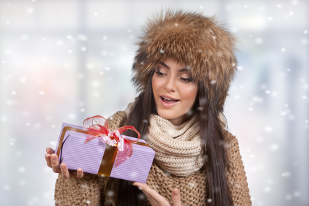 Beautiful young girl with a gift in their hands, basks in winter christmas clothes, sweater and hat on a white background. Studio portrait. Standard-Bild