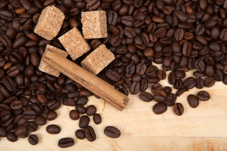 enticement: Coffee beans, cane sugar and cinnamon on a wooden plank.