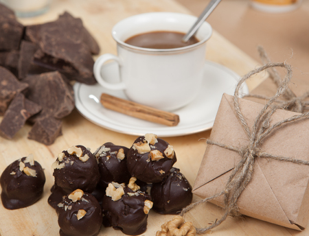 enticement: Pieces of chocolate, cane sugar, cup of coffee and sweets truffle on a wooden board. Stock Photo