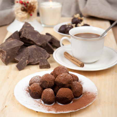 tempt: Pieces of chocolate, cane sugar, cup of coffee and sweets truffle on a wooden board. Stock Photo