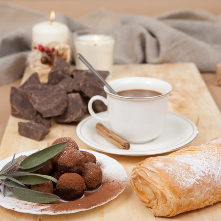 tempt: Pieces of chocolate, cane sugar, cup of coffee and sweets truffle with bake on a wooden board. Stock Photo