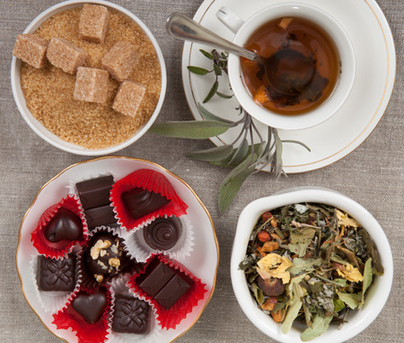 enticement: Cup of tea, cane sugar, cinnamon, and chocolate candies on a linen cloth. Stock Photo