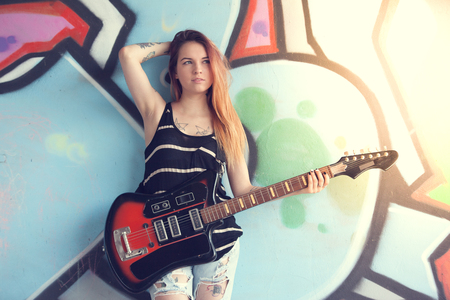 solar flare: Girl teen with electric guitar stands near the wall of graffiti. Solar flare in the frame. Stock Photo