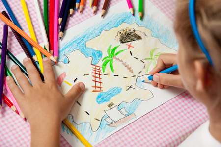 Child paints a picture of pencils pirate treasure map. Crayon. 스톡 콘텐츠