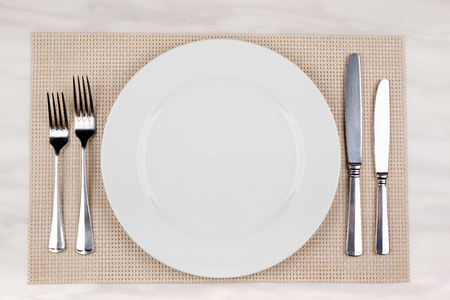 Empty white plate with cutlery is on the table. Knives and forks on both sides of the dishes.