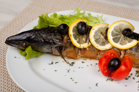 Stuffed fish with lemon and olives on a white dish. 版權商用圖片