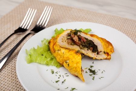 Baked stuffed chicken roll with green salad.