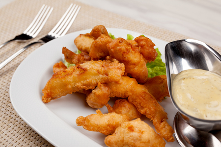 Fried chicken fillet nuggets with sauce on a white plate. 版權商用圖片