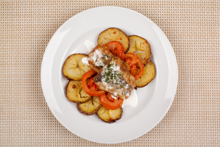 Baked potatoes in the peel sliced with tomato and grilled meat in a white sauce. 版權商用圖片