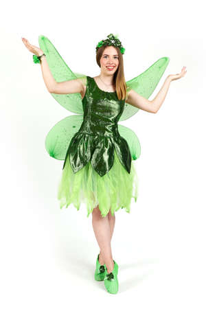 A young girl dressed as a forest fairy with wings in the studio on a white background.