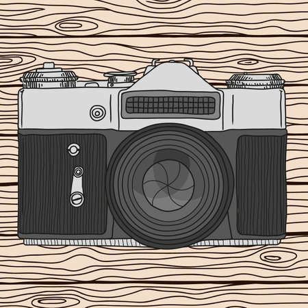 Vector sketch of a film retro camera with a lens on the background of wooden boards. Vector illustration on a beige.