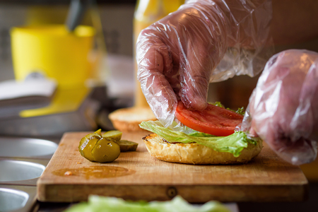 Making Homemade Maxi Burger with grilled beef steak, lettuce, cheese, tomato, onion, barbecue sauce, honey mustard, pickles Stock Photo - 80258097