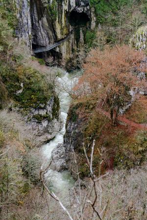 Skocjanske Jame Looking Towards The Deep Gorge With Cave Entrance And Walking Paths. Village Of Skocjan In The Background.