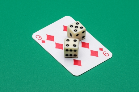 Playing card and two dice isolated on green background photo