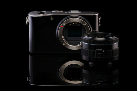 Mirrorless camera body with opened sensor and lens on black background with reflection