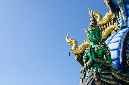 sua: Thai Tradition Green Male Angel Sawasdee (Hello) with Blue Sky at Wat Rong Sua Ten Chiang Rai Thailand.  Most Visited from Tourist.