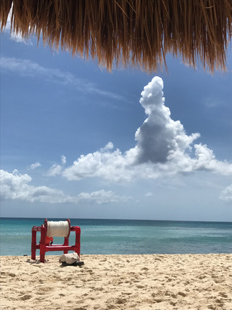 View from the hammock and under a palapa of the Caribbean Sea, with a capstan and clouds in front Stock Photo