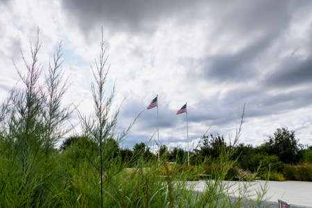 It is an area located on the top of a cliff on the Normandy coast, view of the vegetation two flags and the cloudy sky