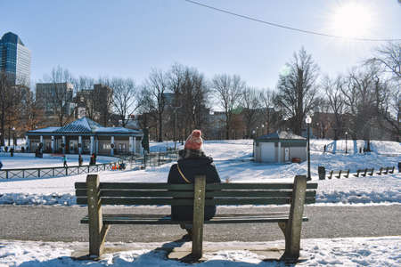 Girl sitting on a bench contemplates the snowy park on a sunny winter day