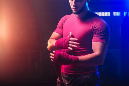 strong man wrapping his hands with boxing hands tape - close up - fight, sport and boxing themes