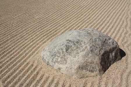 Sand with texture and design with a big rock