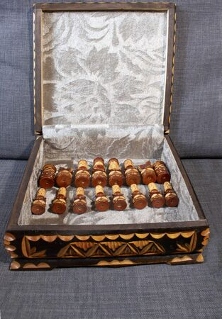 Chess box with black chips, made of carved wood. The interior of the box lined in gray fabric with decorations