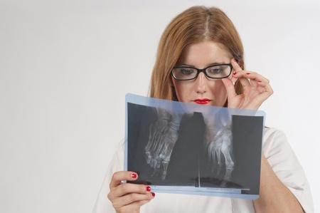 Doctor en examen de una pelirroja de rayos-X Foto de archivo