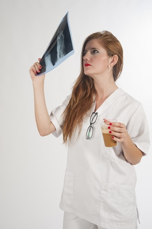 Doctor examining an X-ray redhead, and a coffee Stock Photo - 13344817