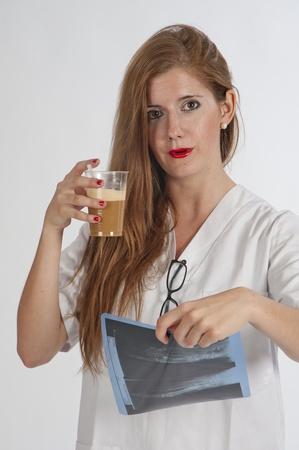Doctor en examen de una pelirroja de rayos X, y un café