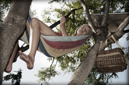 Teenager lying in a hammock hanging from the tree