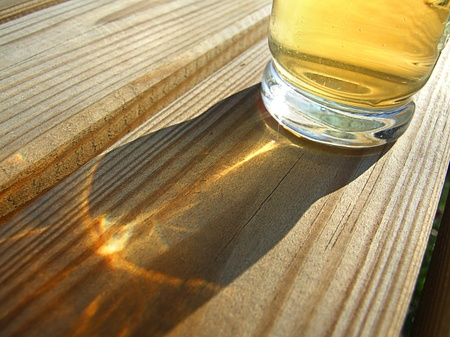 One glasses of cold beer backlit on the wooden table