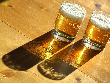 Two glasses of cold beer backlit on the wooden table  Foto de archivo