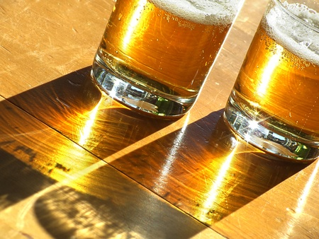 Two glasses of cold beer backlit on the wooden table  Stock Photo