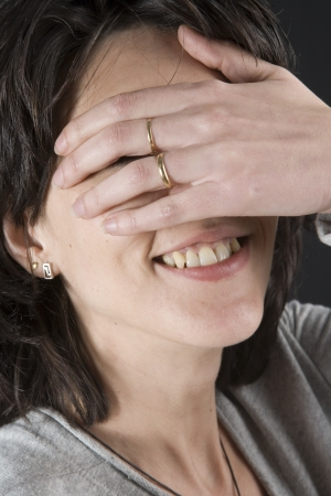 Brunette woman smiling and covering her eyes photo