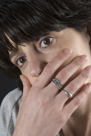 Closeup of a dark woman with hand on mouth photo