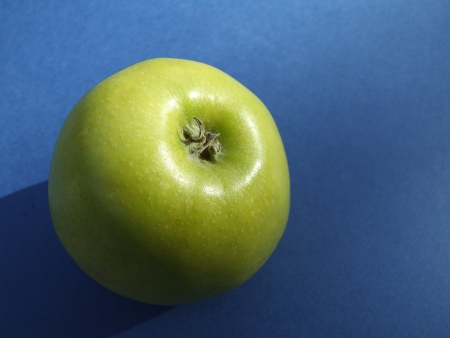 Green apple on a blue tablecloth